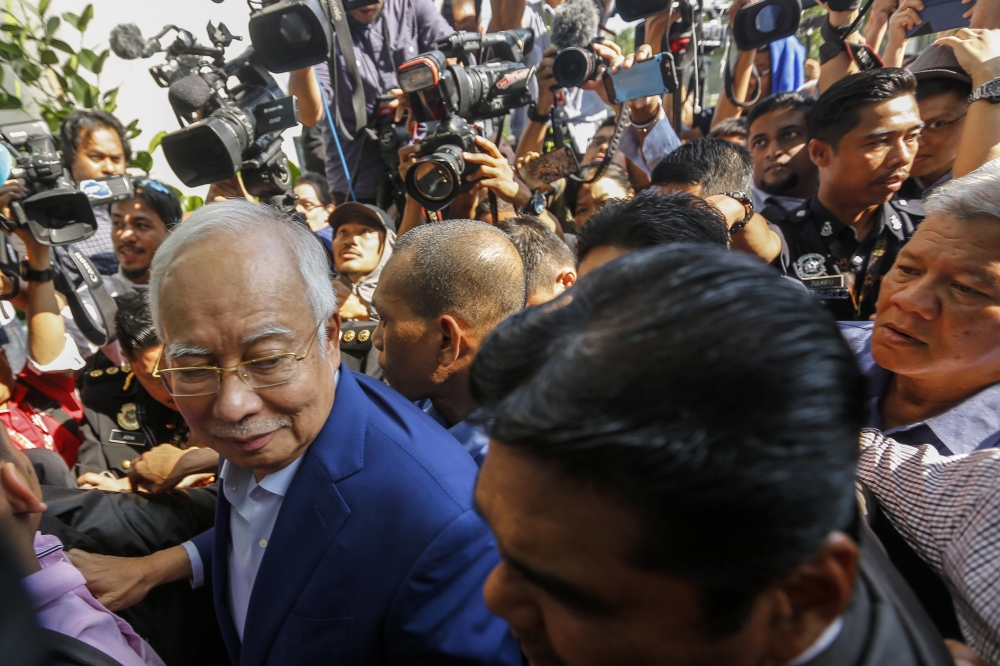Former Malaysia Prime Minister Najib Razak, left, surrounded by media as he arrives at the Malaysian Anti-Corruption Commission (MACC) in Putrajaya, Malaysia, on Tuesday. — EPA