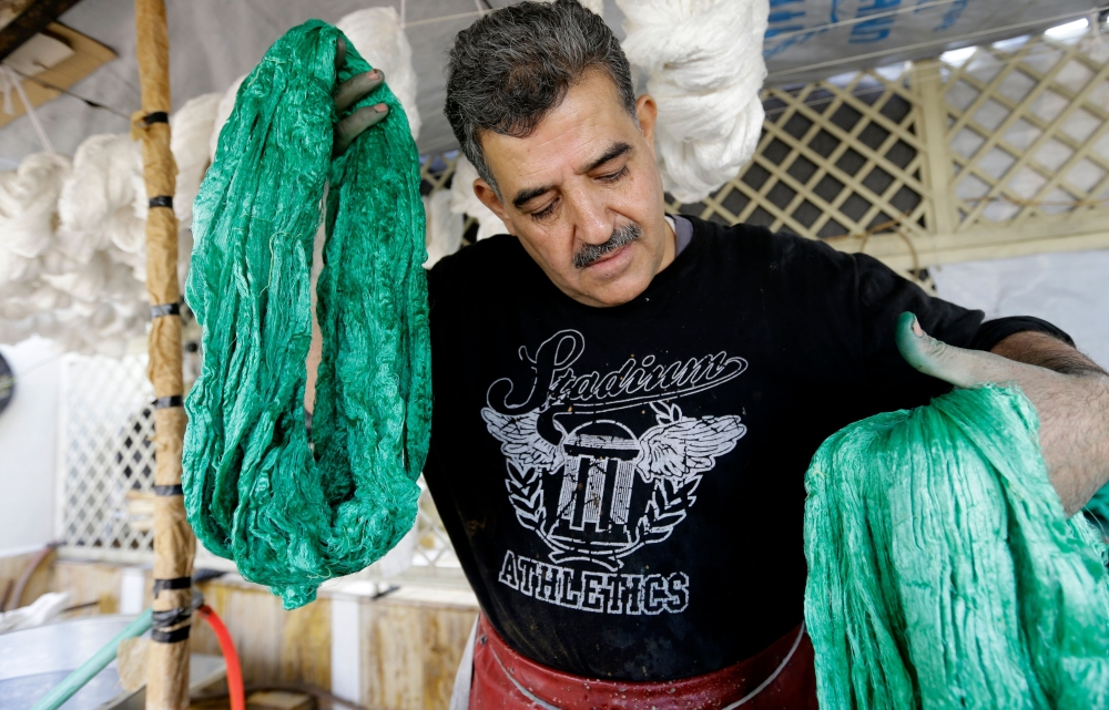 Mohammad Al-Rihawi dips silk threads into green dye at his atelier in the Syrian capital Damascus. — AFP