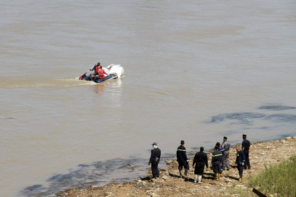 Iraqi civil defense workers recover a body from the Tigris river in the northern Iraqi city of Mosul. — AFP