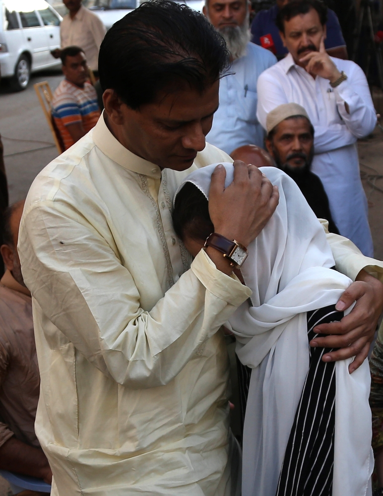 Abdul Aziz Sheikh, father of Sabika Sheikh, an exchange student from Pakistan who was killed in shooting at school in Texas, US, comforts relatives during her funeral in Karachi, Wednesday. — EPA