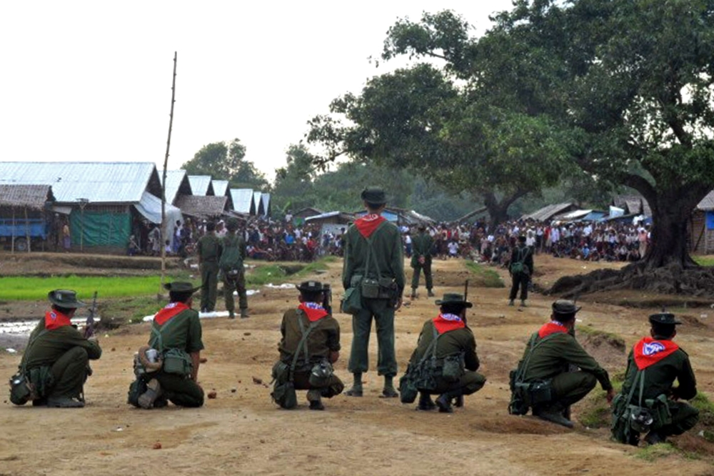 Myanmar security force personnel stand guard while a mob (background) looks on following unrest at an Internally Displaced People's (IDP) camp for Muslim Rohingyas on the outskirts of Sittwe town in Rakhine state.