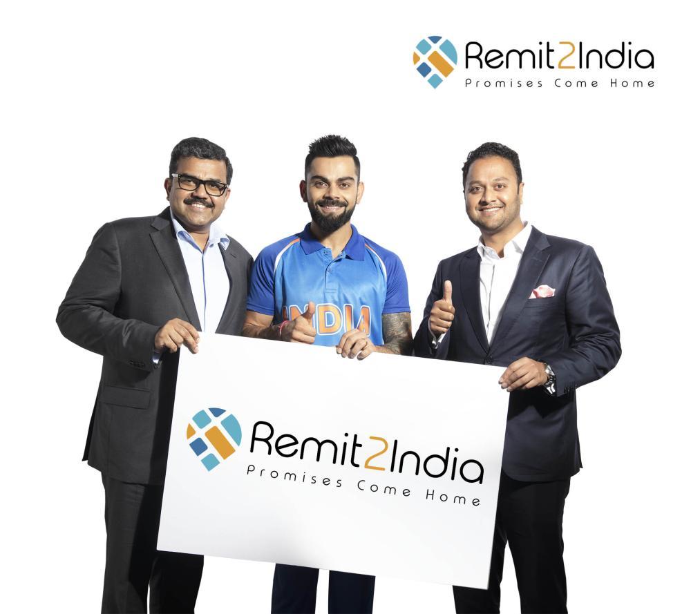 Indian Cricket Captain Virat Kohli with Finablr Executive Director Binay Shetty (right) and Finablr Executive Director Promoth Manghat (left). — Courtesy photo