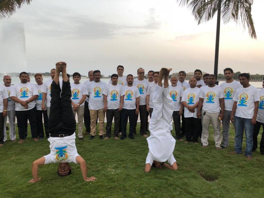 Indian Consul General Md. Noor Rahman Sheikh (right) performs the head stand  at the Red Sea beach area with the iconic 300 meters King Fahd Fountain in the backdrop.