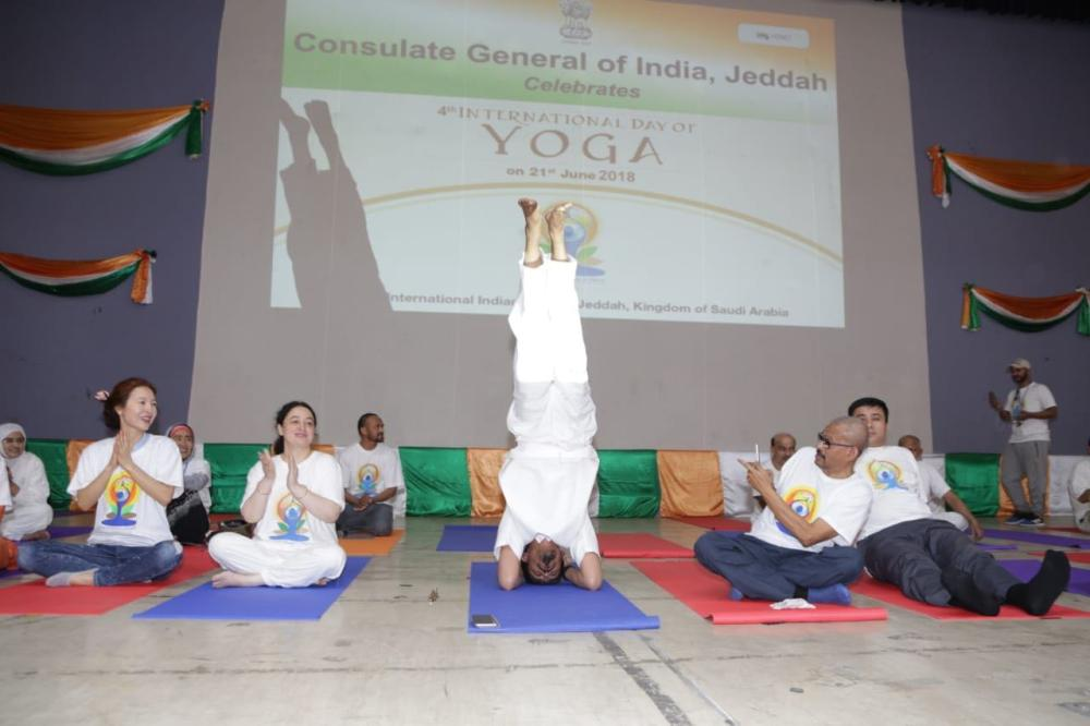 Indian Consul General Md. Noor Rahman Sheikh performs the head stand at the auditorium.