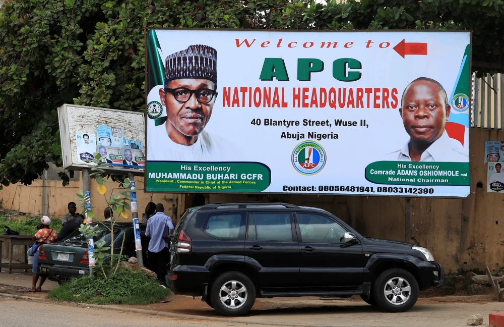 People stand near a sign for the All Progressive Congress (APC) national headquarters in Abuja, Nigeria, on Thursday. — Reuters