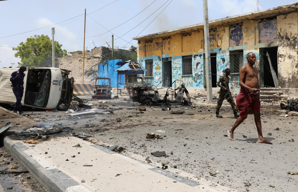 An unidentified man walks from the scene of a suicide car bombing near Somalia's presidential palace in Mogadishu, Saturday. — Reuters