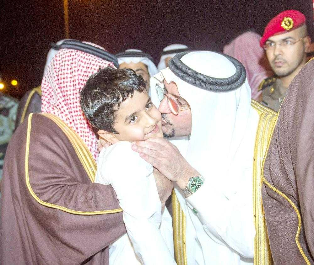 Emir of Qassim Prince Faisal Bin Mishal kisses one of the policeman's children during the visit.