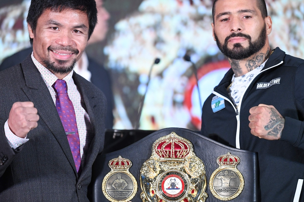 Philippine's Manny Pacquiao (L) and Argentina's Lucas Matthysse (R) pose for pictures with the welterweight championship belt after the press conference on Thursday, ahead their fight on Sunday. — AFP