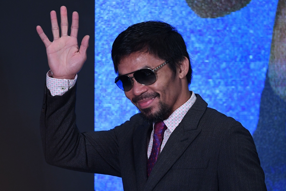 Philippine's Manny Pacquiao waves as he arrives for a press conference in Kuala Lumpur on Thursday, ahead of his world welterweight boxing championship bout against Argentina's Lucas Matthysse on Sunday. — AFP