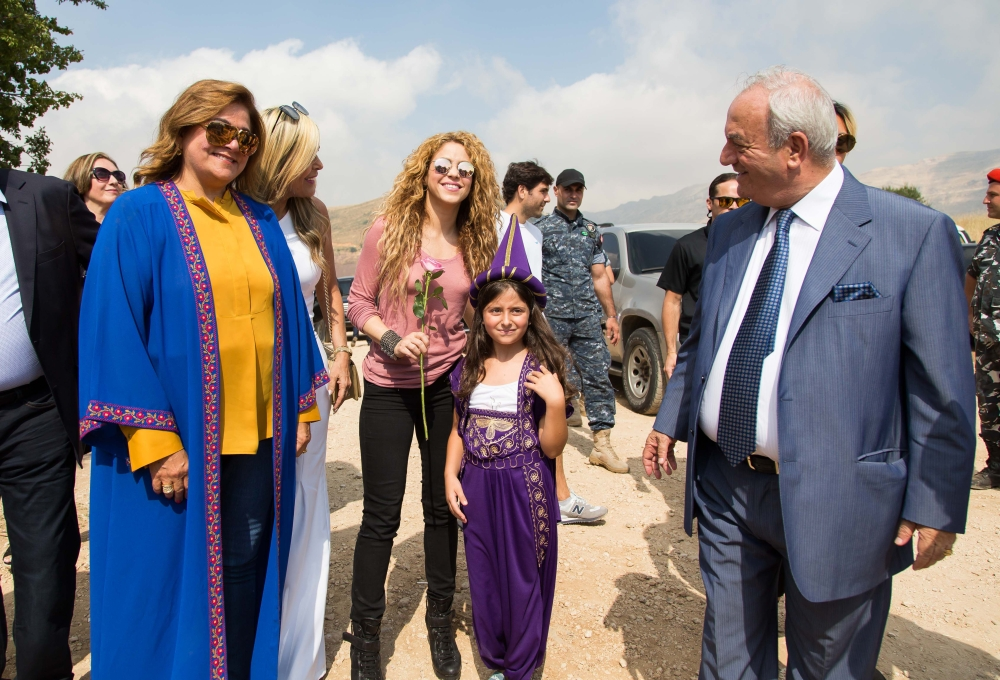 A handout picture provided by the Honorary Consulate of Lebanon in Barranquilla, Colombia, shows Colombian singer Shakira posing for a picture with a girl dressed in traditional Lebanese clothing during her visit to the northern mountain village of Tannourine where her paternal grandmother was born. - AFP