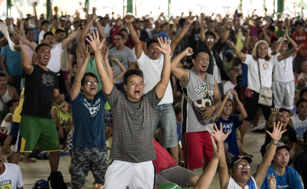 Filipino fans react as they watch Philippines' Manny Pacquiao fight Argentina's Lucas Matthysse during their world welterweight boxing championship bout in Kuala Lumpur, at a basketball court in Manila on Sunday. — AFP