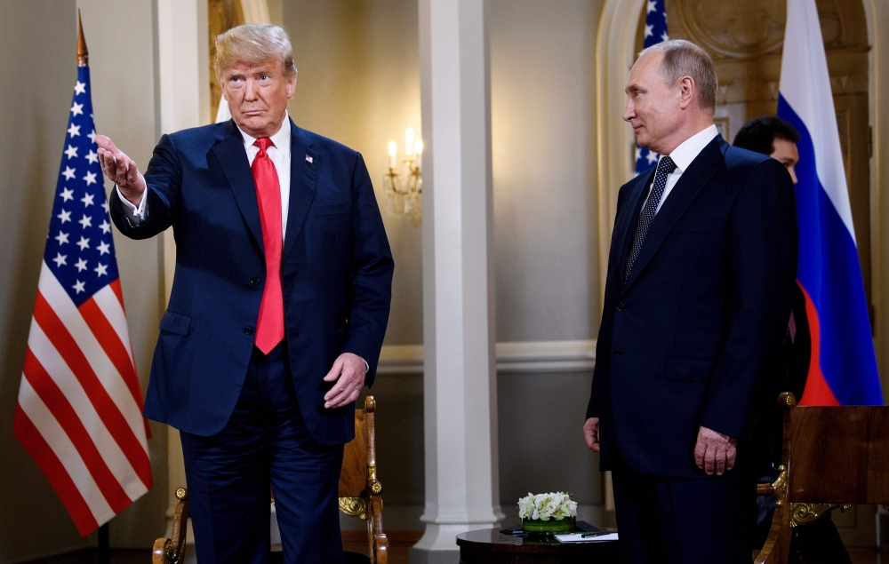 US President Donald Trump (left) and Russia's President Vladimir Putin wait ahead of a meeting in Helsinki, Monday.  — AFP