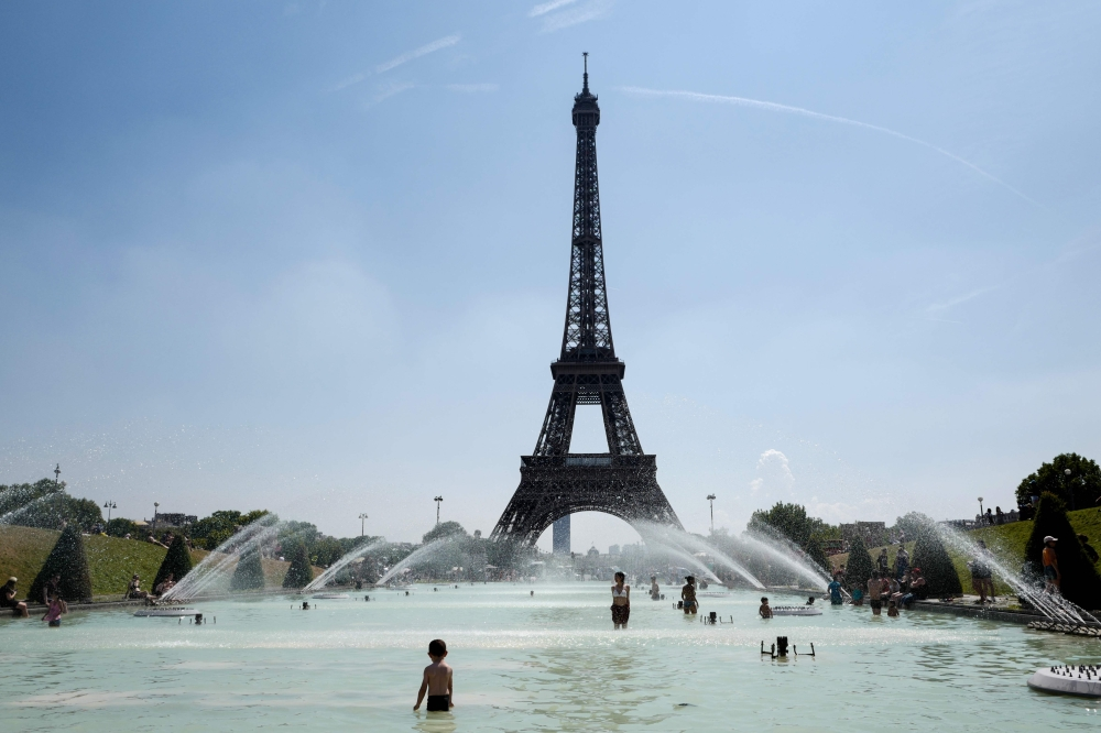 People cool themselves at the Trocadero Fountain in front of The Eiffel Tower in Paris in this July 27, 2018 file photo. — AFP