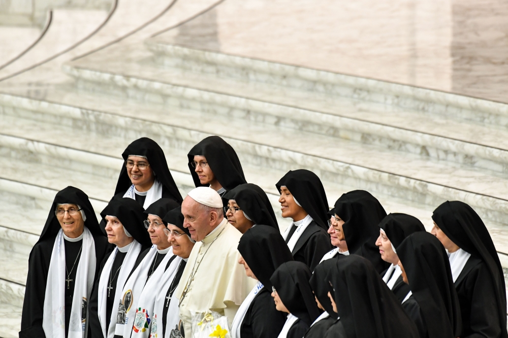 Pope Francis, center, poses for a photo with nuns during his weekly general audience at Aula Paolo VI (Paul VI Audience Hall) at the Vatican on Wednesday. — AFP