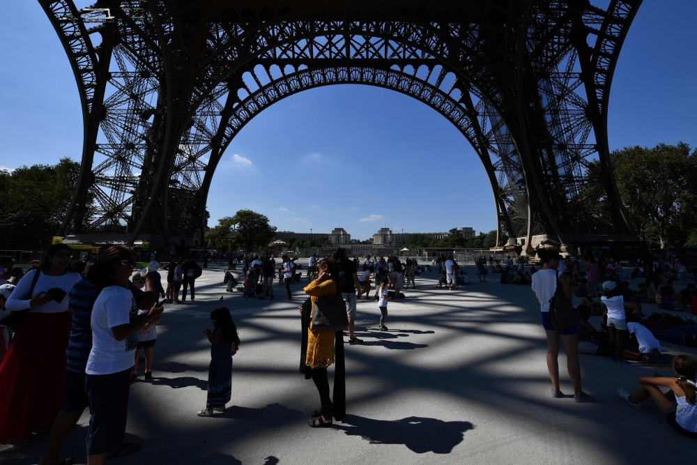 Tourists gather under the Eiffel Tower in Paris on Thursday. — AFP