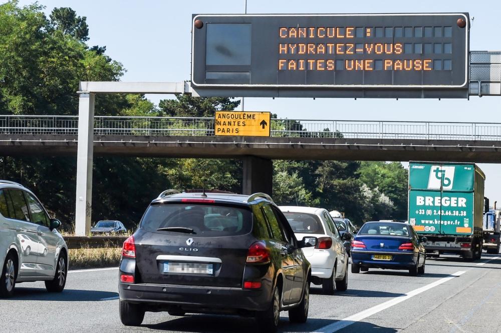 A road billboard displays the message