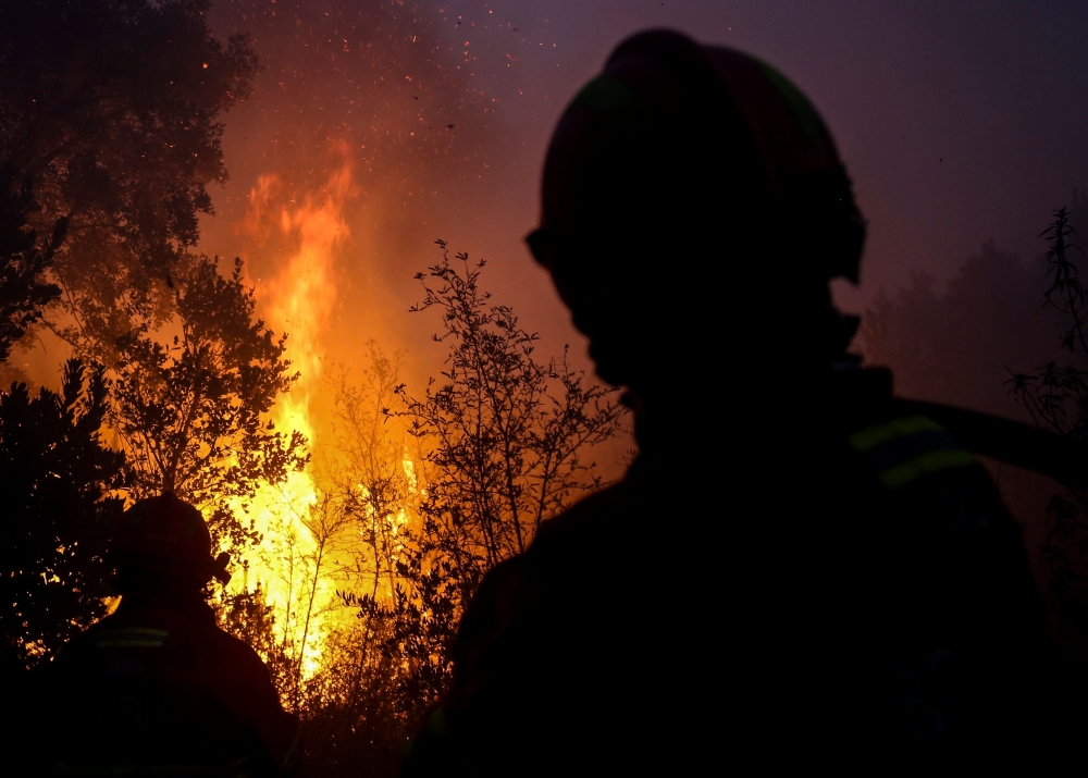 Firefighters watch trees burning in flames as they combat a wildfire close to Monchique in the Portuguese Algarve, on Wednesday. — AFP