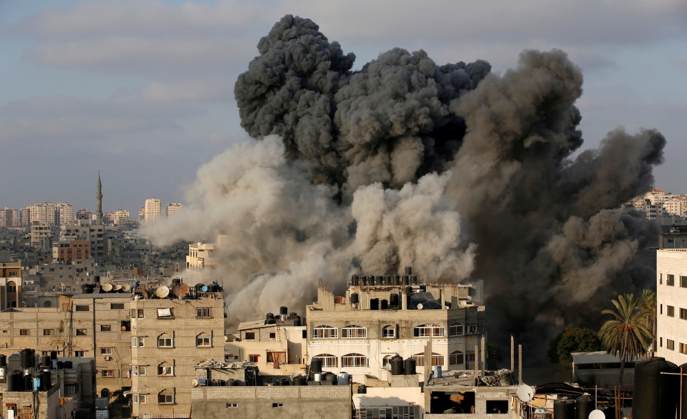 Smoke rises after an Israeli aircraft bombed a multi-story building in Gaza City on Thursday. — Reuters