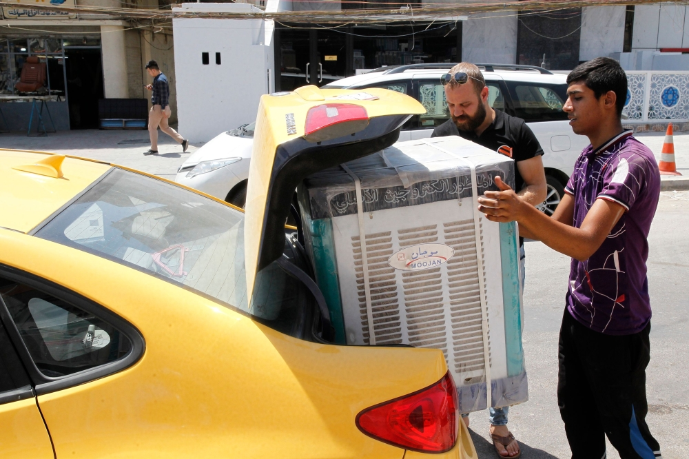 A laborer helps a customer stack an appliance box in his car at a store in Baghdad on Wednesday. — AFP