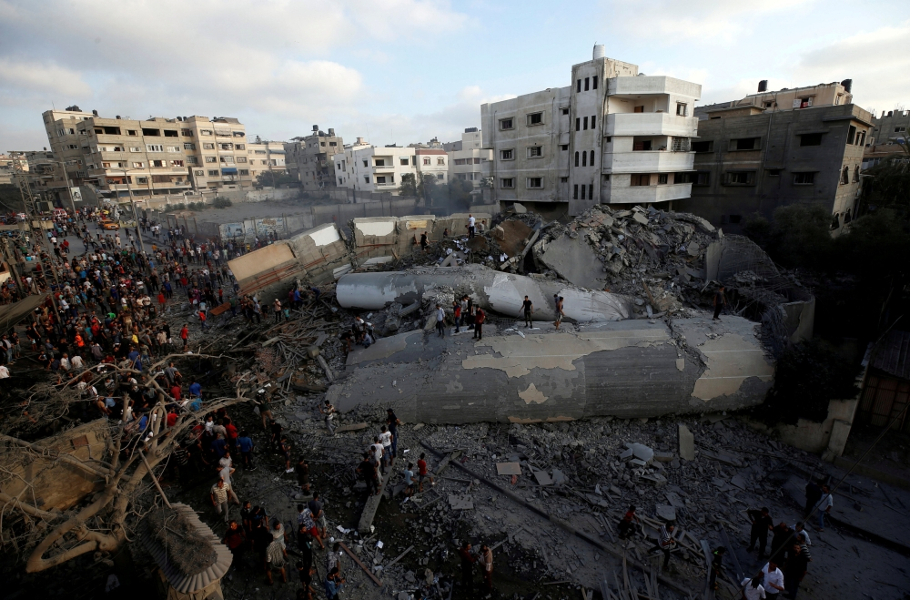 Palestinians gather around a building after it was bombed by an Israeli aircraft in Gaza City on Thursday. — Reuters