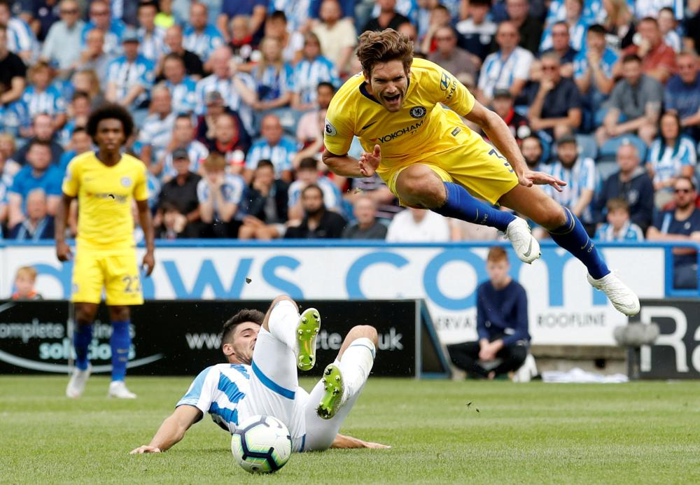 Huddersfield Town's Christopher Schindler fouls Chelsea's Marcos Alonso (top) and a penalty was awarded to Chelsea during their English Premier League match at John Smith's Stadium, Huddersfield, Saturday. — Reuters
