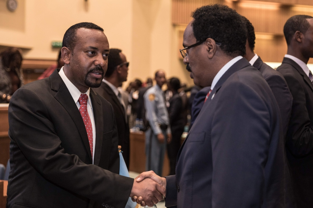 Ethiopia's Prime Minister Abiy Ahmed, left, speaks with Somalia's President Mohamed Abdullahi Mohamed at the 33rd Extraordinary Summit of Intergovernmental Authority on Development in Addis Ababa on Sept. 12, 2018. — AFP