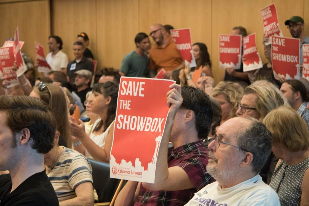 Supporters of music venue The Showbox wave signs at a Seattle City Council meeting. The venue now risks becoming the latest casualty of the Pacific Northwest city's real estate rush - and many in the community are saying enough is enough. - Thomson Reuters Foundation