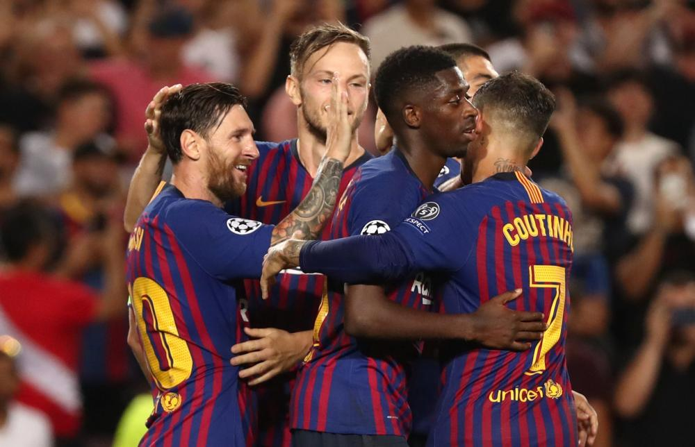 Barcelona's Lionel Messi celebrates with teammates after scoring against PSV Eindhoven during their Champions League match at Camp Nou, Barcelona Tuesday. — Reuters