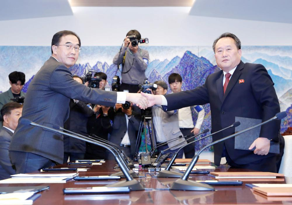 North Korea's Ri Son Gwon, chairman of the Committee for the Peaceful Reunification of the Country, shakes hands with South Korean Unification Minister Cho Myoung-gyon after exchanging the joint statement during their meeting at the truce village of Panmunjom inside the demilitarized zone, South Korea, on Monday. — Reuters