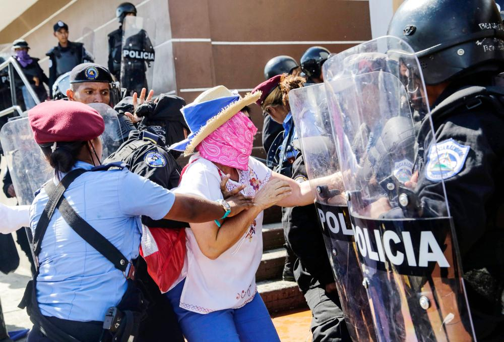A Nicaraguan woman is arrested by riot police during a protest against the government of President Daniel Ortega in Managua on Sunday. — AFP