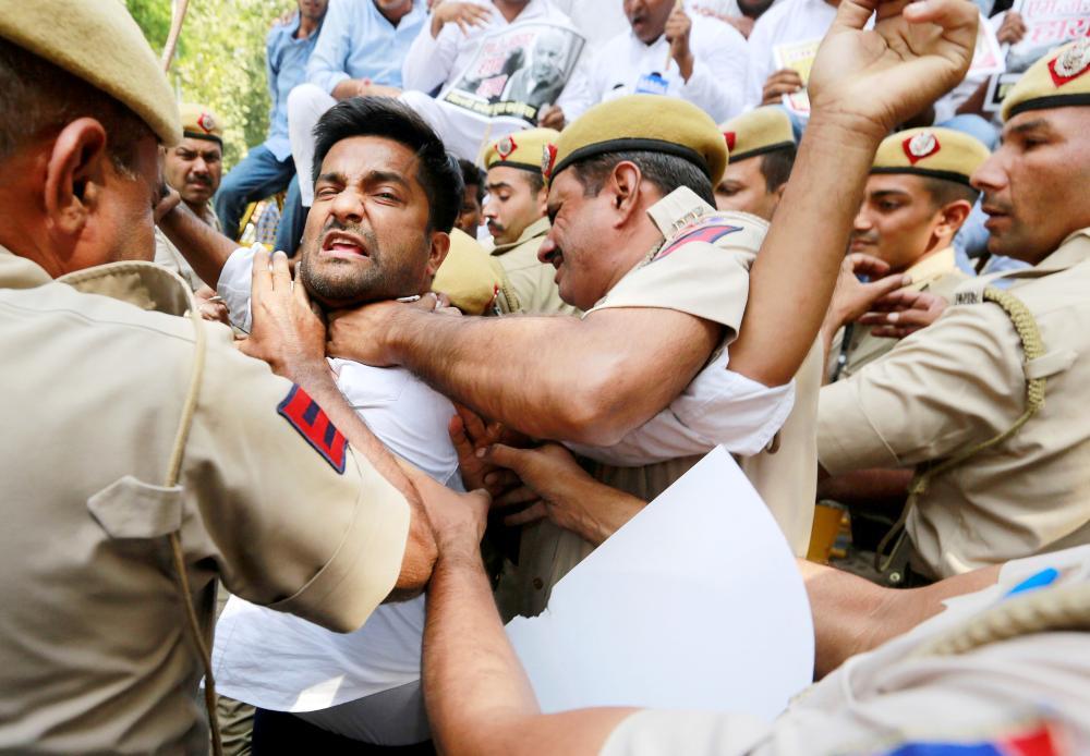 Supporters of India's main opposition Congress party scuffle with police during a protest demanding the resignation of India's Minister of State for External Affairs M.J. Akbar in New Delhi, India, on Monday. — Reuters