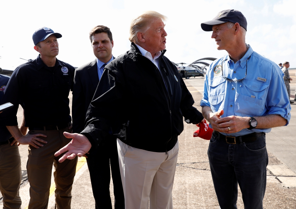 US President Donald Trump stands with FEMA Administrator Brock Long, left, and US Rep Ron DeSantis  as he talks to Florida Governor Rick Scott, right, after the president arrived to tour storm damage from Hurricane Michael at Eglin Air Force Base, Florida, on Monday. — Reuters