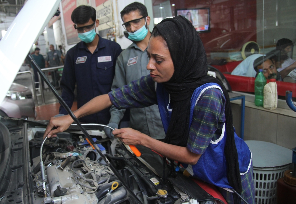 Pakistani motor mechanic Uzma Nawaz, 24, fixes a car at an auto workshop in Multan.  Since picking up a wrench as one of the first female car mechanics in conservative Pakistan, Uzma Nawaz has faced two common reactions: shock and surprise. And then a bit of respect. —AFP