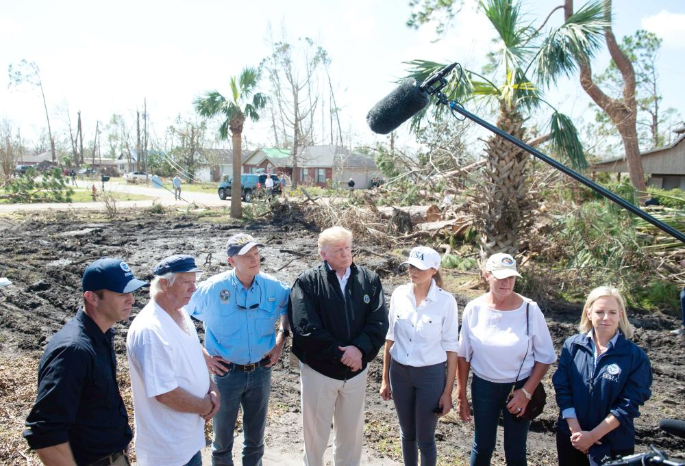 US President Donald Trump and First Lady Melania Trump tour damage from Hurricane Michael in Lynn Haven, Florida, on Monday. — AFP