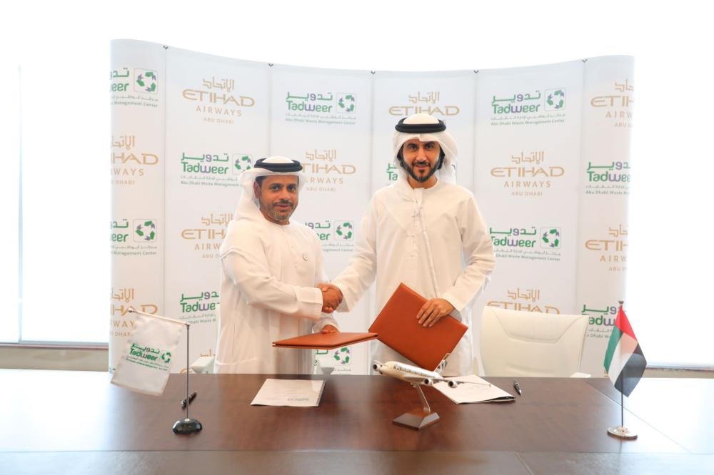 Dr Salem Al Kaabi, acting General Manager of Tadweer, and Mohammad Al Bulooki, Chief Operating Officer at Etihad Aviation Group, shake hands after the signing of agreement