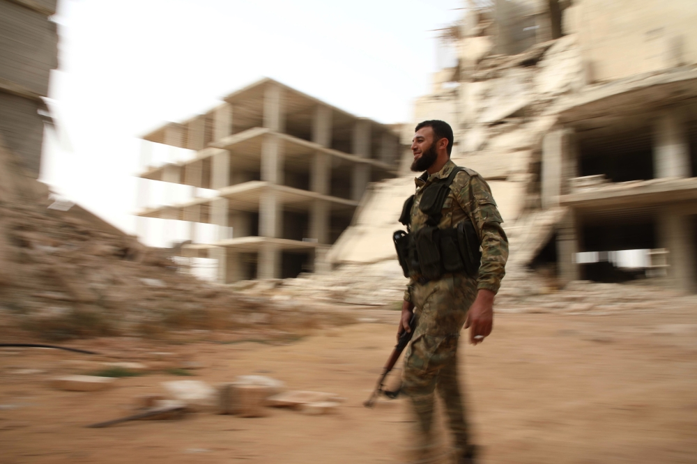 A Syrian rebel-fighter from the National Liberation Front (NLF) walks in a street in the rebel-held Al-Rashidin District of western Aleppo's countryside near Idlib province. Militants in Syria's Idlib failed to meet a deadline to leave a planned buffer zone ringing the country's last rebel bastion, casting fresh doubt over a deal to avert bloodshed. — AFP