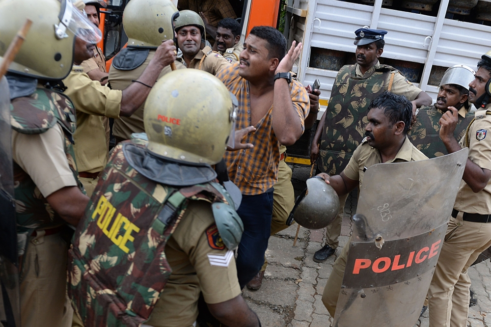 Indian police beat a Hindu activist while they take him into custody as they stop a bus of protesters rallying against a Supreme Court verdict revoking a ban on women's entry to a Hindu temple in Nilakkal in southern Kerala state on Wednesday. — AFP