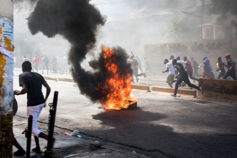 Protesters set fires to block streets as they demonstrate in Port-au-Prince on Wednesday, calling for the resignation of President Jovenel Moise. — AFP