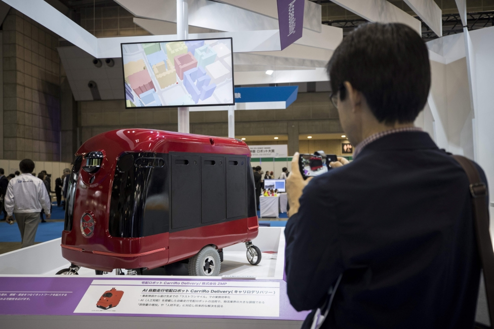 A man takes pictures of a CarriRo robot made by ZMP, which rolls along the pavements and direct itself via GPS to an address within a two-kilometer radius, at the World Robot Summit in Tokyo, on Thursday. — AFP