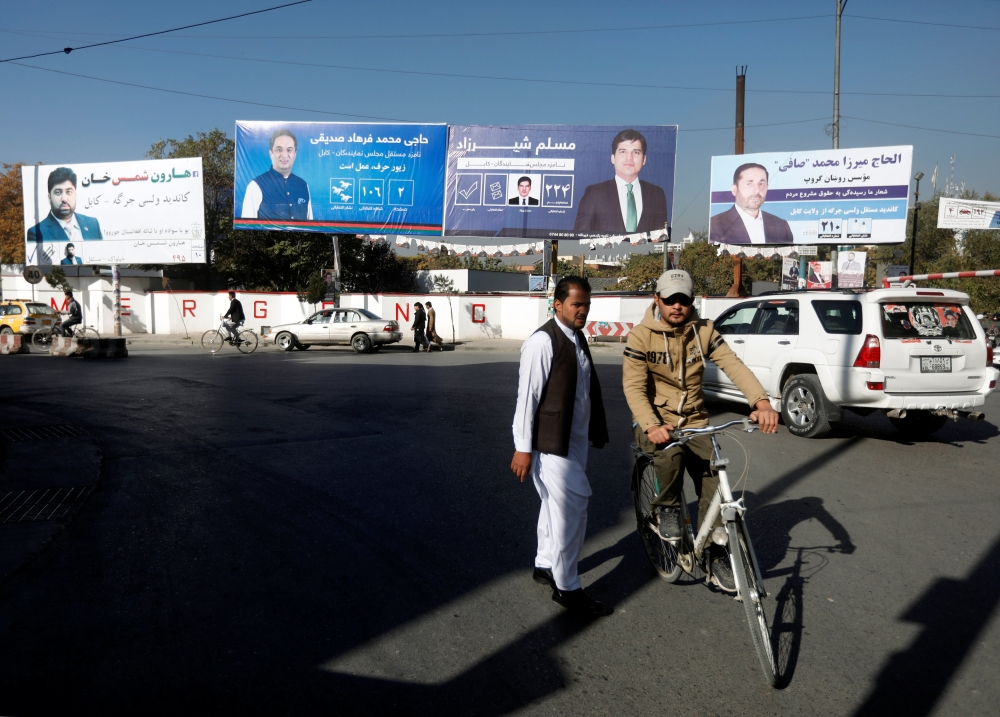 An Afghan man rides on his bicycle in front of election posters of parliamentarian candidates ahead of the elections in Kabul on Thursday. — Reuters
