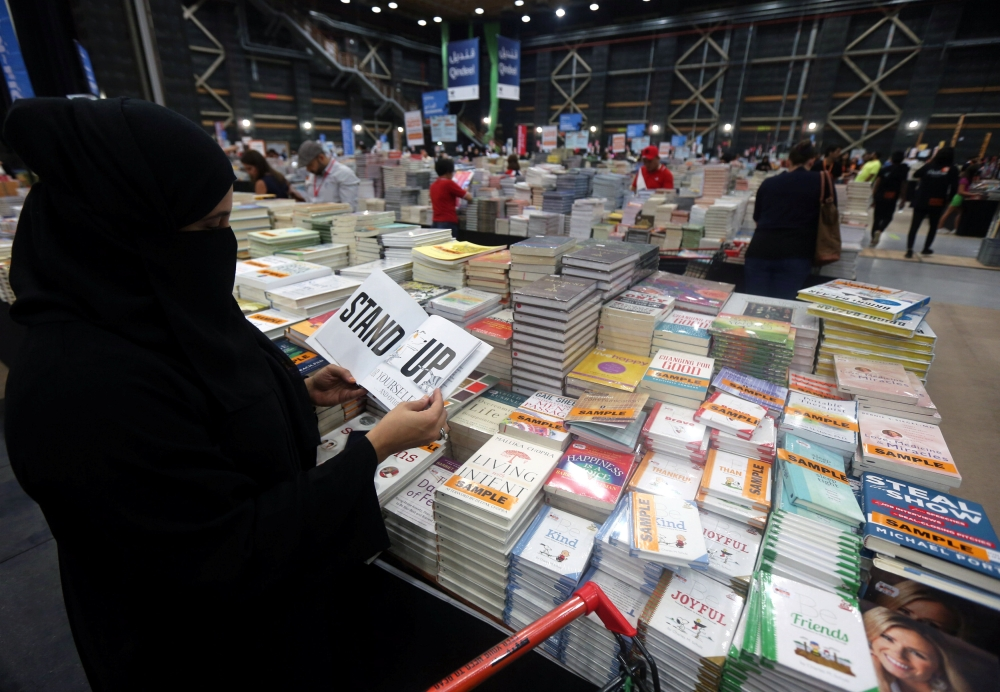 Visitors read books at the Big Bad Wolf Book Sale, which calls itself the world's biggest, hosted for the first time by Dubai, on Wednesday. — Reuters