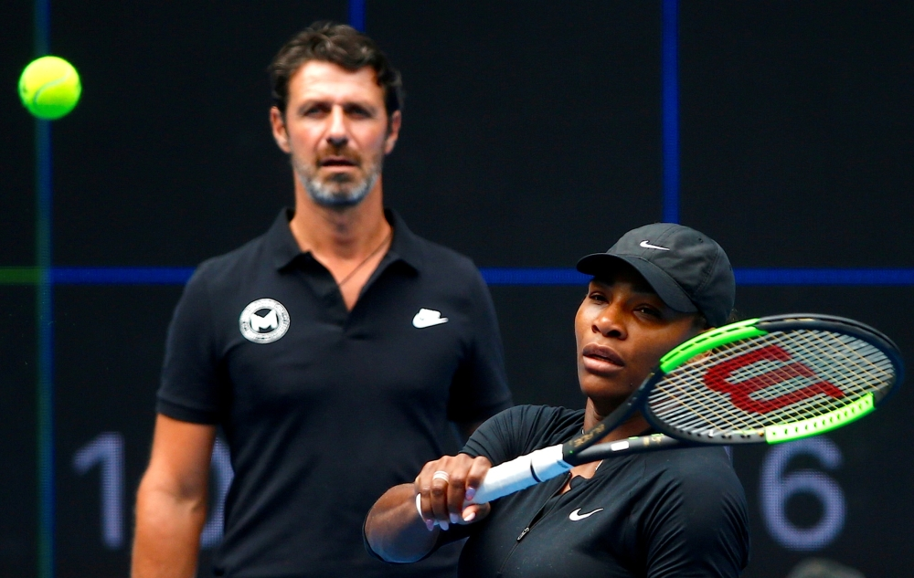 File photo shows Serena Williams of the US hitting a shot as her coach Patrick Mouratoglou looks on during a training session ahead of the Australian Open tennis tournament in Melbourne, Australia. — Reuters