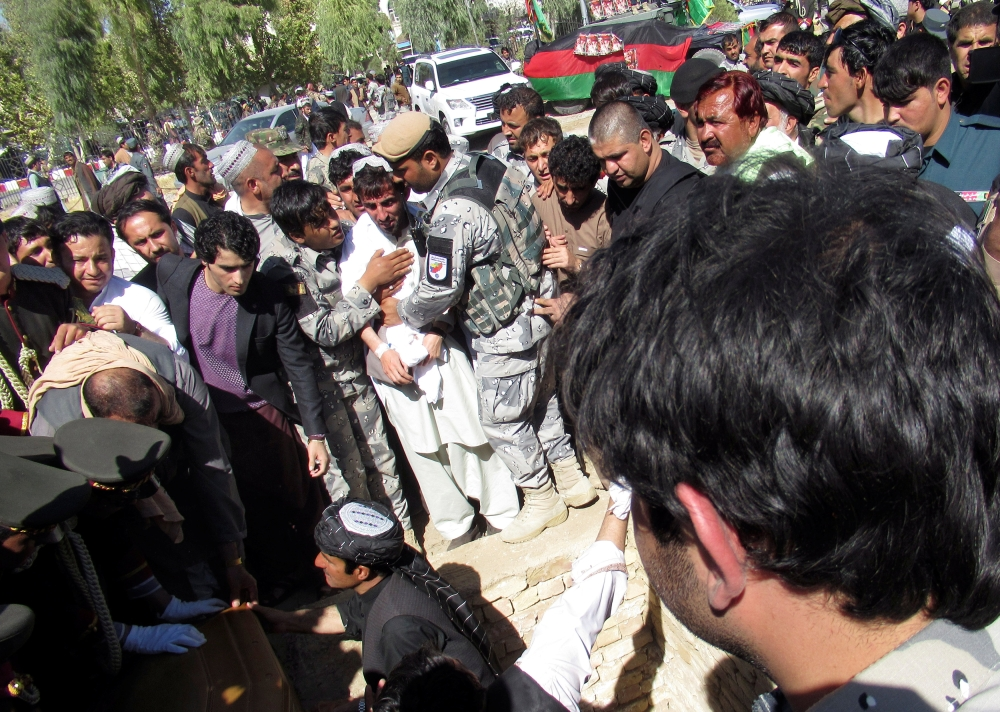People attend a burial ceremony of General Abdul Razeq, the Kandahar police commander, who was killed in Thursday's attack, in Kandahar province, Afghanistan, on Friday. — Reuters