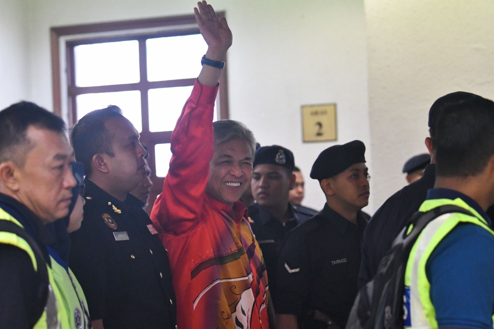 Detained Malaysia's Deputy former Prime Minister Ahmad Zahid Hamidi escorted by police waves before entering a court in Kuala Lumpur to face charges on Friday. — AFP