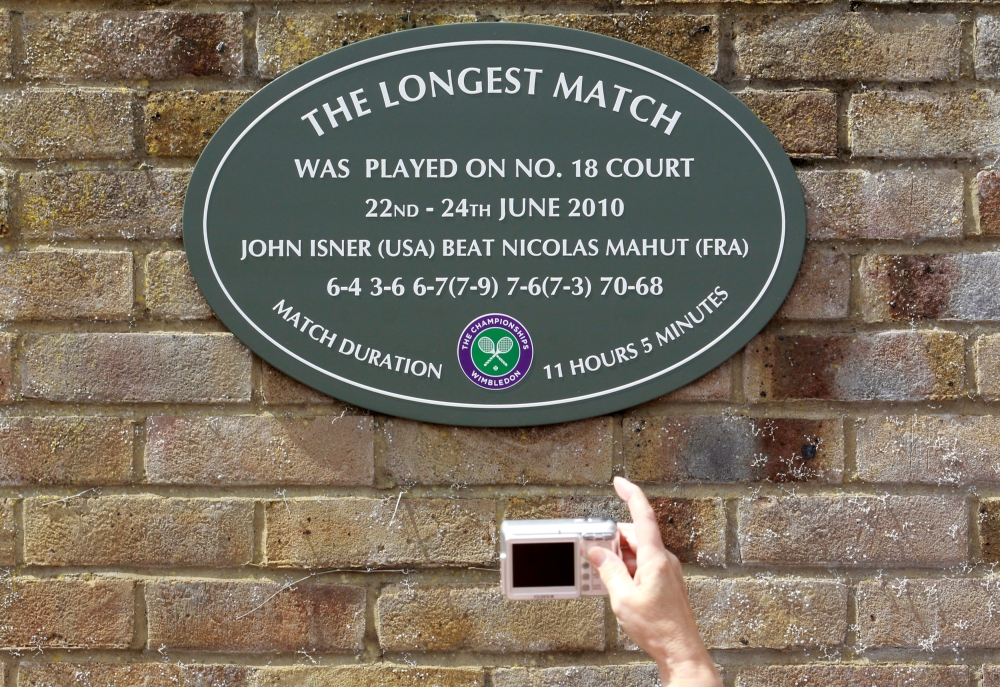 File photo shows a spectator photographing a plaque attached to the wall of No. 18 court after the match in 2010 that lasted more than 11 hours, between John Isner of the US and Nicolas Mahut of France, at the Wimbledon tennis championships in London on June 21, 2011. — Reuters