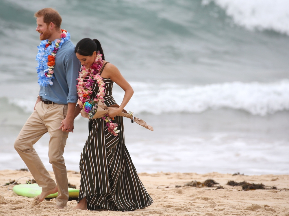 Britain's Prince Harry walks with his wife Meghan, Duchess of Sussex as they meet the local community at Bondi Beach in Sydney on Friday. — AFP
