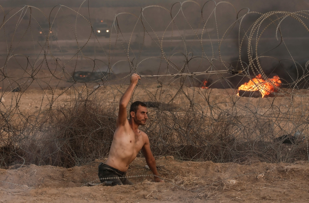 Disabled Palestinian Saber Al Ashqar, aged 29, uses a slingshot to throw stones at Israeli forces during a demonstration near the border with Israel, east of Gaza City, on Friday. — AFP