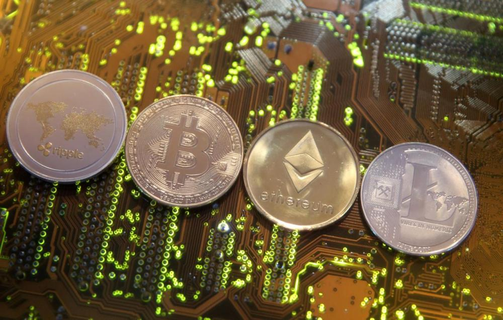 Representations of the Ripple, Bitcoin, Etherum and Litecoin virtual currencies are seen on a PC motherboard in this illustration picture. — Reuters
