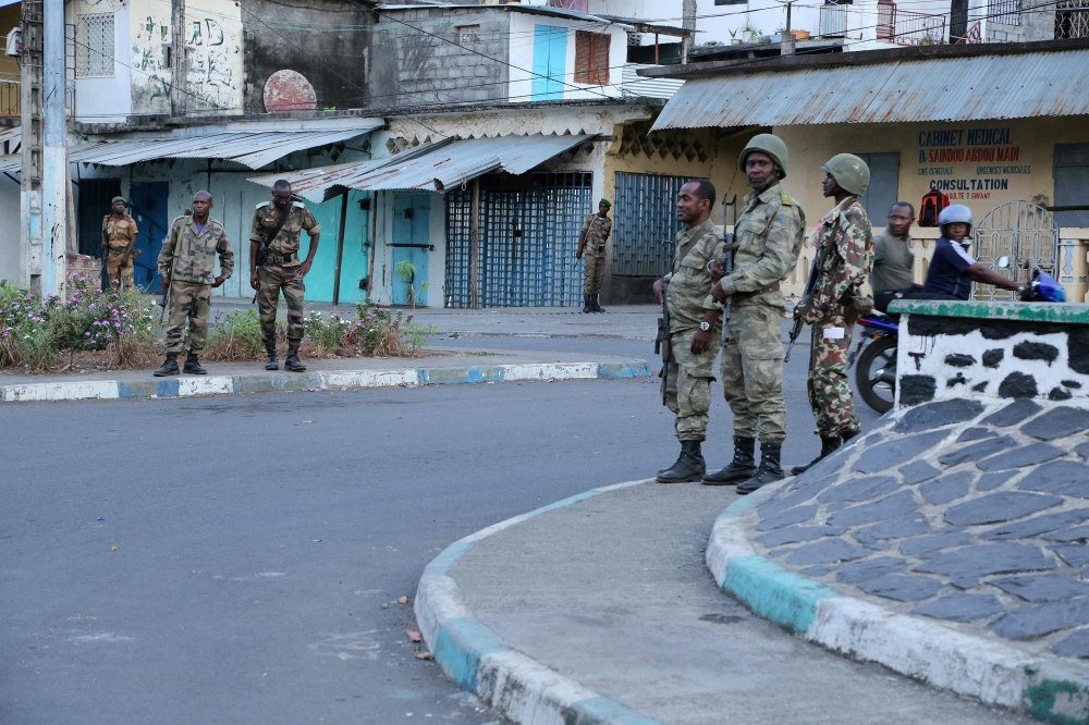 Soldiers from the Comoros armed forces station and wait outside a quarter at Mutsamudu in Anjouan, Comoros, on Friday. — AFP
