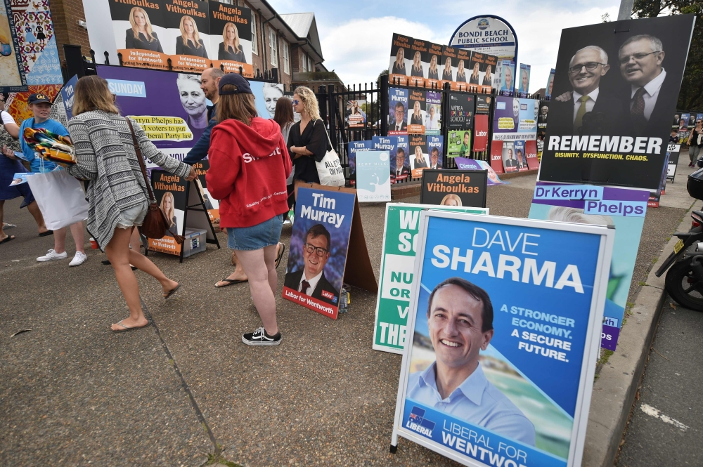 Election posters are seen outside a polling station during the Wentworth by-election in Bondi Beach in Sydney, Saturday. — AFP